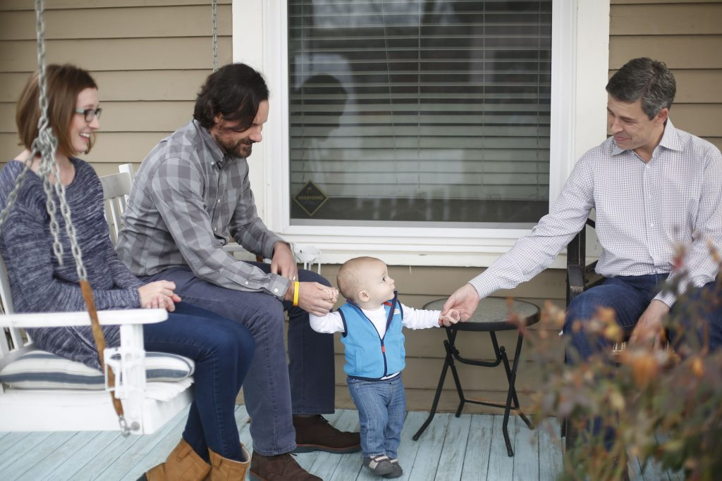 Andy on a porch with a family